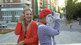 Mime and young girl has fun at fountain background. Mime in red beret and stripped shirt has fun with young girl at fountain background. Street actor entertains stock video