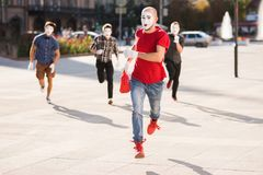 A group of mimes runs after a thief who stole a bag Stock Photo