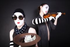 Mimes playing a violin for the money Stock Photos