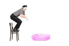 Mimez l'artiste sautant dans une petite piscine gonflable i Photo stock