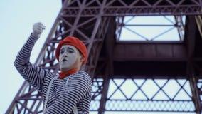 Mimi lo scopritore in berretto rosso e camicia spogliata al fondo della torre Eiffel video d archivio