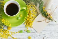 Mimosa, citron och kaffe på ljus träbakgrund Arkivfoto