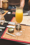 Mimosa next to joint, grinder, lighter, and other cannabis acces. Alcoholic beverage in focus, on table place mat near cannibus and related accessories stock image