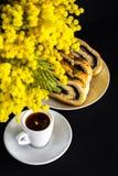 Mimosa, tasse de café et strudel de clou de girofle sur un fond noir Photo libre de droits