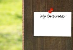 Min affärsinskrift på vitt anmärkningspapper med en träbakgrund Arkivfoton