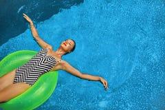 min andra ser sommarsemesterarbeten Kvinna som solbadar och att sväva i simbassängvatten Fotografering för Bildbyråer