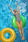 min andra ser sommarsemesterarbeten Kvinna som solbadar och att sväva i simbassängvatten Arkivfoton