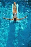 min andra ser sommarsemesterarbeten Kvinna som solbadar och att sväva i simbassängvatten Royaltyfri Bild