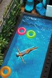 min andra ser sommarsemesterarbeten Kvinna som solbadar och att sväva i simbassängvatten Arkivbilder