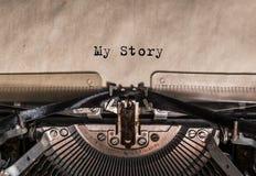 Min berättelse har skrivit ord på en tappningskrivmaskin utskrivavna bokstäver på papper Royaltyfria Bilder