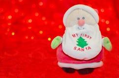 Min första jultomten på röd bokehbakgrund Arkivbilder