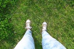 Min gymnastikskor och jeans på det naturliga gräset med hyper perspektiv Royaltyfri Foto
