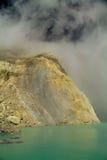 Mina amarilla del sulfuro con el lago azul dentro del volcán, foto de archivo