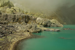 Mina amarilla del sulfuro con el lago azul dentro del volcán, imagen de archivo