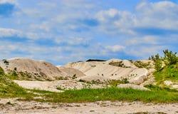 Mina blanca de la piedra caliza en un fondo del cielo azul con las nubes imagen de archivo