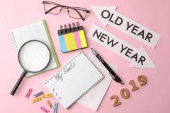 Mina mål 2019 text i en anteckningsbok med kulöra klistermärkear och en penna, exponeringsglas, förstoringsapparat på en ljus ros royaltyfri foto