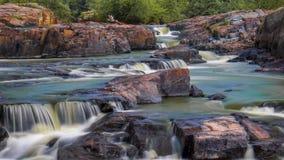 Mina rocosa de la cascada colorida rodeada por intentos verdes y rocas pintadas imagen de archivo