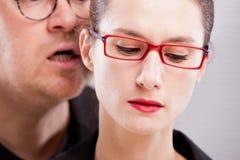 Minacce di sibilo dell'uomo in orecchio della donna Fotografie Stock
