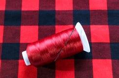 Minaccia rossa con l'ago su tessuto rosso Fotografie Stock