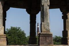 Minar Qutab sett mellan pelare av en chhatri i den arkeologiska mehraulien parkerar Royaltyfria Foton