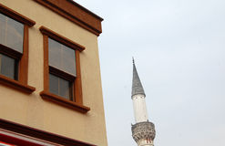 Minaret. Pic of an old minaret and windows of a new house in Skopje, Macedonia Stock Image