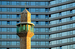 Minaret against hotel. Royalty Free Stock Image
