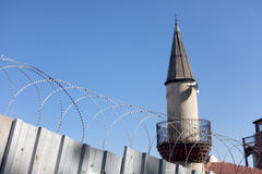 Minaret with barbed wire fence Royalty Free Stock Photos