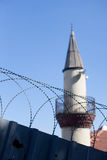 Minaret with barbed wire fence Stock Photos