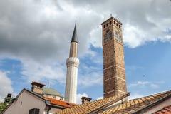Minaret de la mosquée de begova de Gazi Husrev à côté du clocktower du bazar de Sarajevo, en la Bosnie-Herzégovine Photo stock