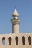 Minaret framme av den Nizwa fortslotten Arkivfoto