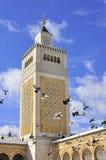 Minaret of the Great mosque in Medina Tunis. With flying pigeons. Al-Zaytuna Mosque, or Ez-Zitouna or Ezzitouna Mosque (Arabic: جامع الزيتونة Stock Photo