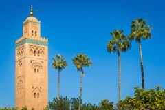 Historic minaret and palm trees. The minaret of the Koutoubia Mosque in a clear, sunny day, Marrakesh, Morocco stock photo