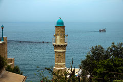 The minaret of the mosque in old Jaffa   on blue sky and  Mediterranean sea background Stock Photos