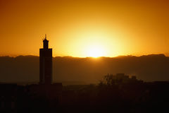 Minaret of mosque with sunset. A minaret of a mosque with sunset as background. Symbol of islam, ramadan, prayer Royalty Free Stock Images
