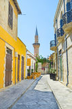 The minaret. The narrow street with the small outdoor cafe and minaret of the Grand Mosque Cami Kebir on the background, Limassol, Cyprus stock photography