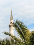 Minaret and palm tree on blue sky Royalty Free Stock Photography