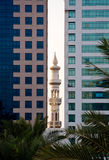 Minaret peeping between office buildings Stock Images