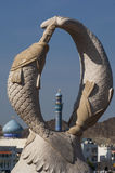 Minaret seen through a double dolphin sculpture Stock Images