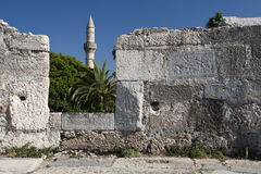 Minaret tower and castle wall in Kos city Royalty Free Stock Images