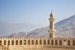 Minarete atrás de uma parede de um forte em Nizwa imagem de stock