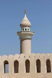 Minareto davanti al castello della fortificazione di Nizwa Fotografia Stock