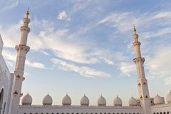 Minarets and domes of the mosque against blue skies. Minarets and domes of the Sheikh Zayed Grand Mosque against blue skies in Abu Dhabi, UAE Royalty Free Stock Photos
