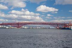 Minato bridge in Osaka Japan. Red suspension bridge over seacoast Royalty Free Stock Images