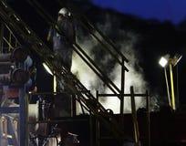 Minatore che lavora all'impianto di perforazione Immagine Stock