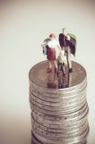 Minatue family on pile of coins. Family budget concept. Macro photo with retro style effect stock images
