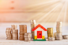 Minature houses resting on pound coin stacks Stock Image