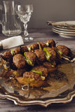 Mince meatball on a spit. (Italian dish) surrounded by glass, dishes and cuttlery, an elegant napkin on the table. everything on a gray wooden table with a gray Stock Photo