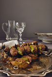 Mince meatball on a spit. (Italian dish) surrounded by glass, dishes and cuttlery, an elegant napkin on the table. everything on a gray wooden table with a gray Royalty Free Stock Images