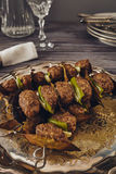Mince meatball on a spit. (Italian dish) surrounded by glass, dishes and cuttlery, an elegant napkin on the table. everything on a gray wooden table with a gray Stock Photos