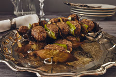 Mince meatball on a spit. (Italian dish) surrounded by glass, dishes and cuttlery, an elegant napkin on the table. everything on a gray wooden table with a gray Royalty Free Stock Image